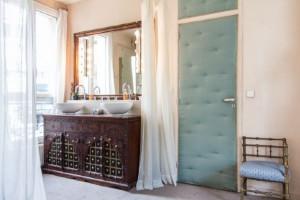 Les vasques étant dans la chambre, elles ne devait pas ressembler à une salle de bains classique. D'où l'idée de détourner un meuble indien chiné dans une brocante en posant juste des vasques dessus. Seul un voilage sur câble les sépare de la chambre. La porte capitonnée en plus d'être esthétique, sépare la pièce phoniquement du reste de l'appartement. Quand on a trois enfants, c'est indispensable !