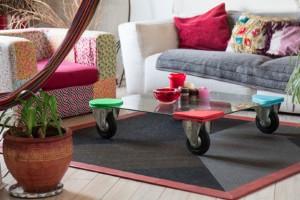 """Le coin salon est constitué d'un fauteuil acheté à la Braderie de Lille, recouvert de tissus façon patchwork par Mops qui a également fabriqué la table basse à partir d'une plaque en verre. Elle est posée sur le tapis ONE de la collection """"Cocotte Power pour Artepy"""" design Mops également."""