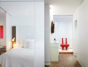 Une entrée en dammier de bois de bout, une chambre avec baldaquin de voilage fixé dans des rails dans le plafond...