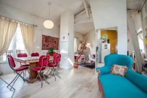 Comme une maison à l'envers, c'est sous les toits que se trouve l'espace à vivre avec les chambres en-dessous. La hauteur sous plafond, la charpente peinte en blanc et le mobilier coloré personnalisé en font un loft funky et unique.