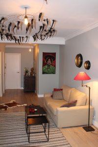 Un lustre de créateur, un mur de couleur, un tapis, une table basse et quelques éléments de décoration ont transformé cet appartement en cocon cosy