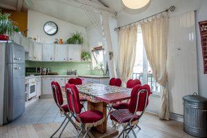 La cuisine ouverte sur la pièce doit son côté vintage à l'habillage des rangements en bois cérusé bleu ciel et son réfrigérateur Smeg. Achetée 15 euros à l'Armée du Salut, nous avons recouvert personnellement la table de mosaïque pour en faire une création unique.
